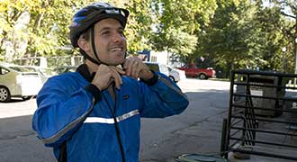 man wearing bicycle helmet to reduce the amount of injury if in a bicycle accident with a car
