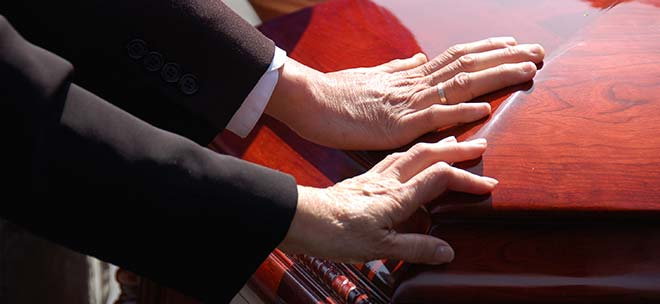 Loved one with hands on coffin of loved one and needing a Massachusetts Wrongful Death Lawyer